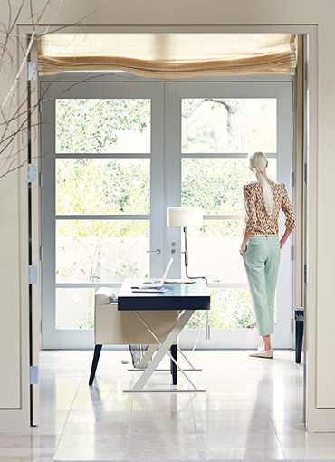 Woman looking out her triple pane window french door